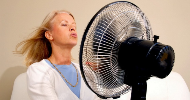 Frau kühlt sich mit einem Ventilator ab Woman with Hot F lushes Model-Released